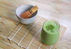 Viftar smoothien Matcha för grönt te med stenbunken och trä på bambu som är matt på tabellen Arkivfoto