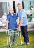 Vigilante feliz que ayuda a la mujer mayor a utilizar a Zimmer Imagen de archivo libre de regalías