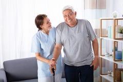 Vigilante que ayuda al hombre mayor mientras que camina en casa fotos de archivo libres de regalías