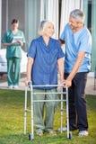 Vigilante que ayuda a la mujer mayor a utilizar caminar Imágenes de archivo libres de regalías
