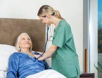 Vigilante que examina a la mujer mayor en la clínica de reposo Foto de archivo libre de regalías