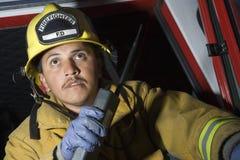 Vigile del fuoco che ha conversazione sul walkie-talkie Fotografie Stock Libere da Diritti