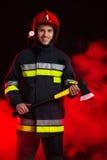 Vigile del fuoco in fumo che posa con l'ascia. Fotografia Stock
