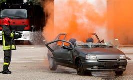 Vigile del fuoco mentre fuori da un fuoco di un'automobile Fotografia Stock