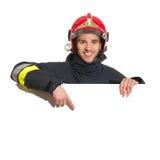 Vigile del fuoco sorridente in casco rosso che indica all'insegna in bianco Immagini Stock