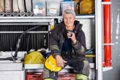 Vigile del fuoco sorridente che si siede in camion alla caserma dei pompieri Immagine Stock