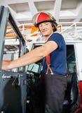 Vigile del fuoco sorridente che sta sul camion Fotografia Stock