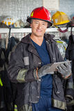 Vigile del fuoco sorridente che tiene la compressa di Digital alla caserma dei pompieri immagini stock libere da diritti
