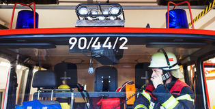 Vigile del fuoco in un camion dei vigili del fuoco e scintilla con l'insieme di radio Immagine Stock