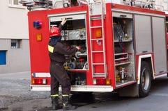Vigile del fuoco vicino ad un'autopompa antincendio Fotografie Stock