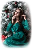 Vignetted picture of a beautiful model girl in a green dress near a decorated Christmas tree keeps her hands on her face. New Year royalty free stock photography