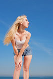 Vigorous long-haired girl outdoors. Long-haired blond woman in shorts and white shirt outdoors Stock Image
