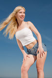 Vigorous long-haired girl outdoors. Long-haired blond woman in shorts and white shirt outdoors Stock Photo