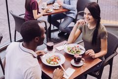 Vigorous lovely couple eating healthy food. Natural food. Top view of glad happy couple eating salad while sitting at cafe and women touching her face Stock Images