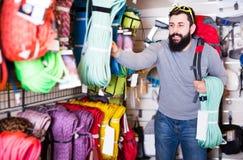 Vigorous male customer examining climbing equipment in sports eq Stock Image