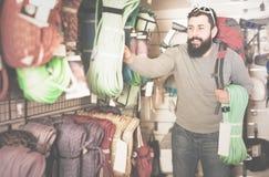 Vigorous male customer examining climbing equipment in sports eq Royalty Free Stock Photo