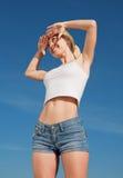 Vigorous smiling girl outdoors. Vigorous blond woman in shorts and white shirt outdoors Royalty Free Stock Image