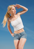 Vigorous smiling girl outdoors. Long-haired blond woman in shorts and white shirt outdoors Stock Images