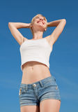 Vigorous smiling girl outdoors. Vigorous blond woman in shorts and white shirt outdoors Royalty Free Stock Photography