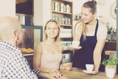 vigorous waiter girl brought cup of coffee for couple of different aged people royalty free stock image