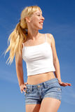 Vigorous young blond woman on background of sky Royalty Free Stock Images