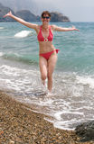 Vigorous young woman running along seashore Stock Image