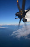 Vigorously rotating plane propeller in the sky. Flying passenger airplane with clear deep blue sky and sea separated by clouds in the background seen from inside Stock Image