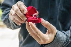 Vigselring i en special ask, håll i händerna av brudgummen Mannen ger en cirkel med en diamant i en ask Royaltyfria Foton