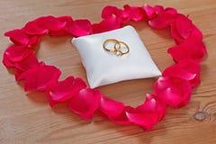 Vigselring och en röd rosa petalhjärta royaltyfri foto