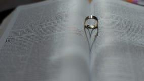 Vigselring som bildar hjärtaform på den öppna bibeln arkivfilmer