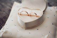 Vigselringar är i en ask i formen av en hjärta Royaltyfri Bild