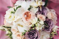 Vigselringar är på en bröllopbukett Royaltyfri Bild