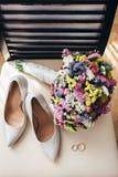 Vigselringar bredvid bride&en x27; s-skor och bröllopbukett Royaltyfria Foton