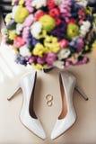 Vigselringar bredvid bride&en x27; s-skor och bröllopbukett Arkivbilder