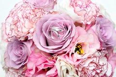 Vigselringar för vit guld på buketten av rosor Fotografering för Bildbyråer
