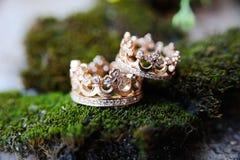 Vigselringar i formen av en krona med juvlar royaltyfria foton