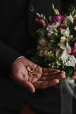 Vigselringar i handen av brudgummen Arkivbild