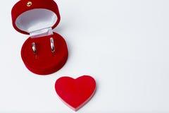 Vigselringar i röd ask på vit bakgrund Royaltyfria Bilder
