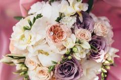 Vigselringar ligger på en bukett av nya blommor Royaltyfria Bilder