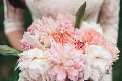 Vigselringar ligger på en bukett av nya blommor Arkivfoto