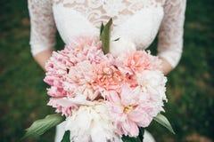 Vigselringar ligger på en bukett av nya blommor Arkivbilder