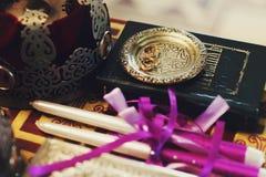 Vigselringar ligger på en guld- platta bak kronan och stearinljus på Arkivbild