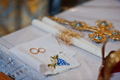 Vigselringar med stearinljus och kors på kyrklig bröllopceremoni Royaltyfri Fotografi