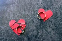 Vigselringar och bruten röd hjärta Svart bakgrund Begrepp av skilsmässan Arkivfoto
