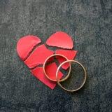 Vigselringar och bruten röd hjärta Svart bakgrund Concen Arkivfoto
