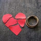 Vigselringar och bruten röd hjärta Svart bakgrund Concen Royaltyfri Foto