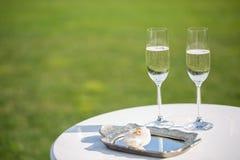 Vigselringar och exponeringsglas av champagne arkivfoto