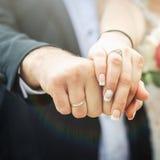 Vigselringar och händerna av brudgummen och bruden Fotografering för Bildbyråer