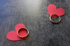 Vigselringar och röd hjärta Svart bakgrund Begreppet av Arkivbilder