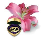 Vigselringar och rosa lilja Royaltyfri Foto
